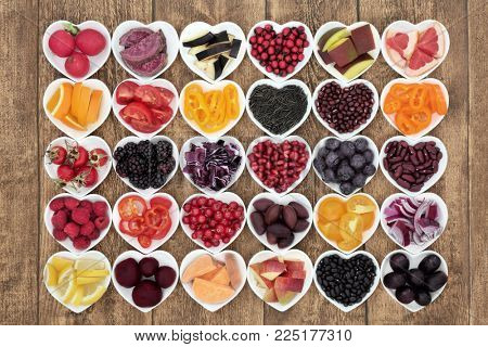 Healthy diet food concept with super health promoting properties in heart shaped bowls, high in antioxidants, anthocyanins, vitamins and minerals on rustic wood background. Top view.