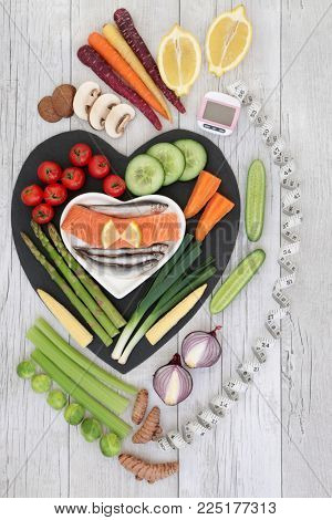 Health diet food concept with fresh fish, vegetables and fruit with pedometer and calorie counter and measuring tape. High in omega 3, antioxidants, anthocyanins, vitamins and dietary fibre.