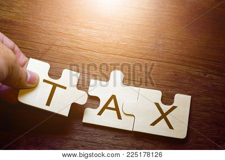 Hand holding wooden jigsaw puzzles with the word