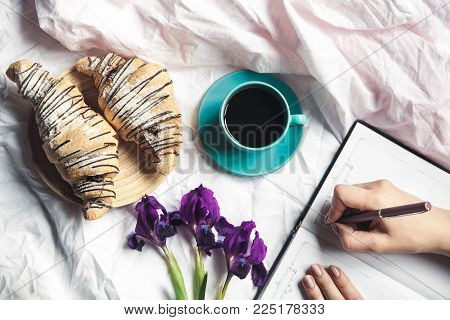 Breakfast in bed, a croissant with coffee and flowers in bed, take notes in a notebook a