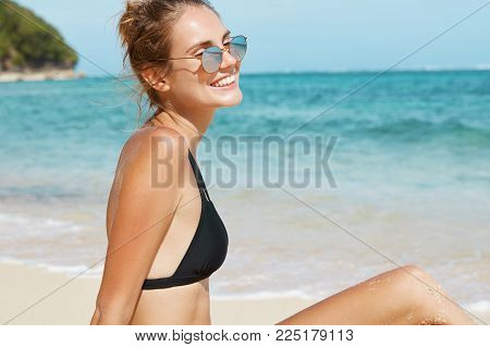 Sideways Portrait Of Beautiful Relaxed Young Carefree Woman In Sunglasses And Swimsuit Sits On Warm