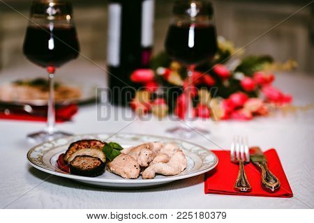 Close up table served for romantic dinner for two with glasses of red wine, roasted chicken fillet with vegetables on plate and flowers. St.Valentine's concept