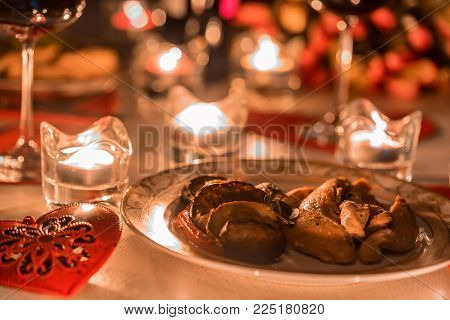 Close up table served for romantic dinner for two with glasses of red wine, roasted chicken fillet with vegetables on plate, flowers and lit by candles. St.Valentine's concept