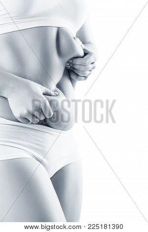 Woman in white underwear holds belly fat. Isolated on white.