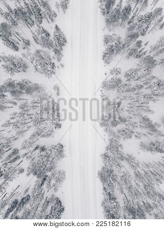 Aerial Drone View Of Winter Forest And Road Covered With Snow.