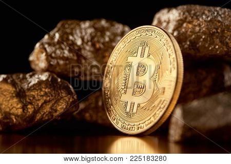 Encrypted golden bitcoin together with gold lumps representing most important finance trends worldwide. Bitcoin as biggest cryptocurrency and digital money. Virtual money blockchain innovation finance