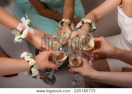 The bride and bride's maidens are sitting in a circle and clink glasses. Hands with flower bracelets. Cropped image