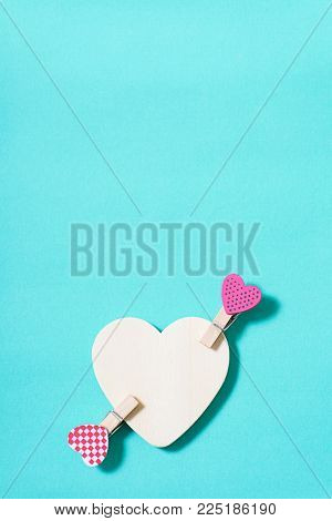 White heart with decoration clothes pegs (heart shape) on green pastel background