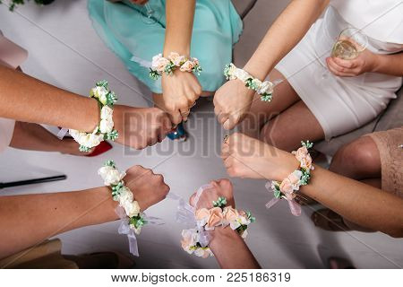 The bride and bride's maidens are sitting in a circle and holding their fists. Hands with flower bracelets. Cropped image