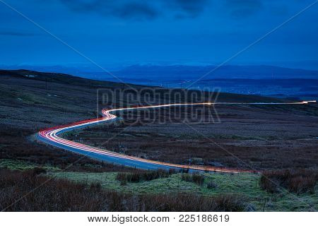 Car Light Trails on Hartside Pass, in the North Peninnes, Cumbria with Eden Valley and the snow capped mountains of the Lake District beyond