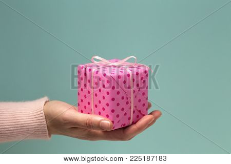 Woman's hand holding a gift. Presenting of gift box wrapped with pink paper in polka dots on blue background. Minimal style. Side view, close up. Happy Holidays, Valentine's, Birthday, New Year
