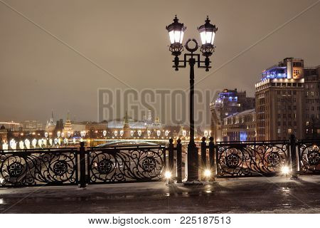 View of the Moscow Kremlin and Estrada Theater from the Patriarchal Bridge and an openwork fence on a winter evening.