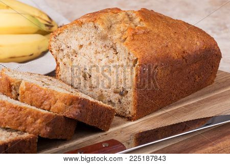 Sliced banana nut bread on a cutting board with bananas in background