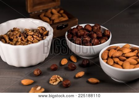 Two white cups filled with nuts, almonds, hazelnuts, walnut and a wooden casket with almonds, on grey wooden table