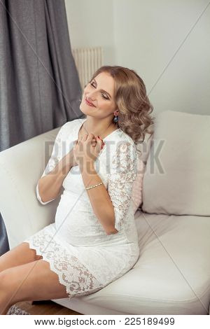 Young beautiful pregnant woman is resting at home. It's cozy. Portrait of a young happy pregnant woman. Pregnancy. Motherhood.