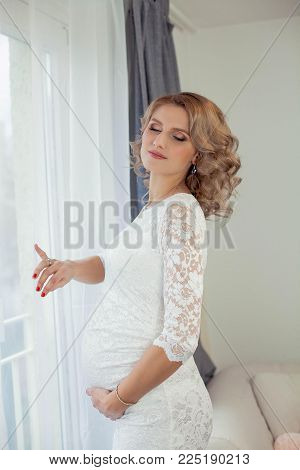 Young beautiful pregnant woman is resting at home. It's cozy. A young woman is standing by the window. Pregnancy. Motherhood.