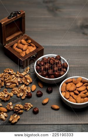 Two white cups filled with nuts, almonds, hazelnuts, walnut and a wooden box with almonds, on grey wooden table