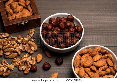 Two white cups with nuts, almonds, hazelnuts, walnut and a wooden box with almonds, on grey wooden table