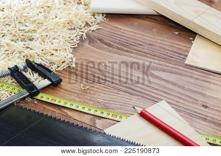 many wooden bricks full of sawdust. On old scratched wooden table, work tools concept.