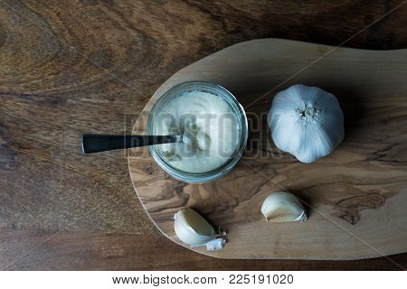 Garlic on a olive wooden plate. on the wooden plate is also a jar with home made aioli