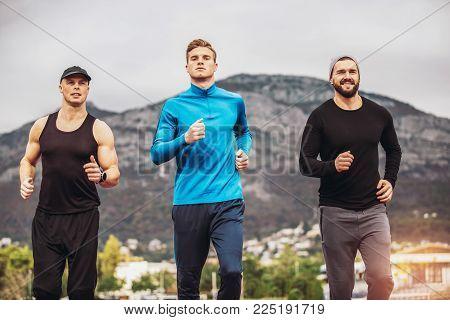 Young athletes practicing a run on athletics stadium track.