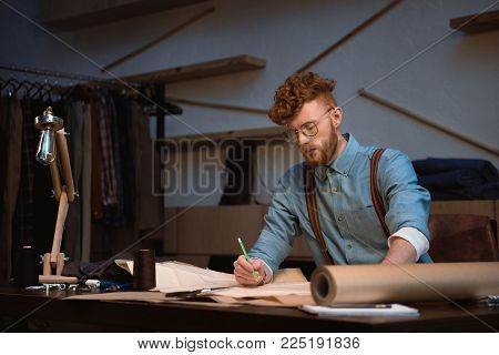 handsome young fashion designer in eyeglasses working with craft paper at workshop
