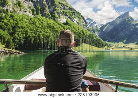 back of rower in front beautiful Seealpsee lake and Alpstein mountain in Appenzell, Switzerland