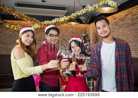 Asian Man And Woman Wear Santa Claus Hat And Holding Champagne Glass On Hand In Christmas Party. Con