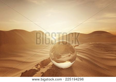 3d rendering of crystal ball on desert landscape with footsteps in the evening sunlight