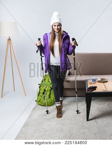 beautiful sportswoman in warm clothing with backpack and hiking sticks at home