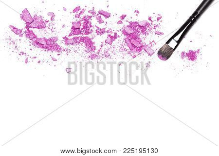 Makeup brush and purple shimmer eye shadow on white with space for text. Make-up background