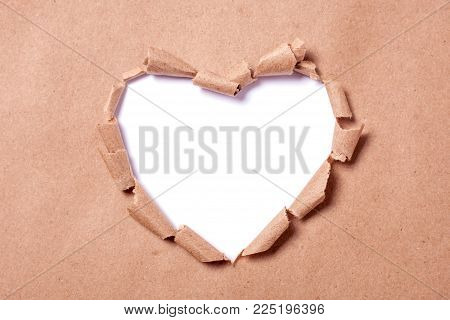 Kraft paper with a hole in the shape of a heart. Hole isolated on white