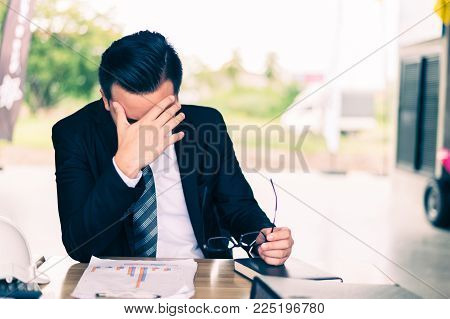 Businessman Sitting And His Hand Clasped Head, He Is Feeling Of Stressed And Sadness, Concept Of Bus