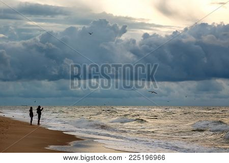Silhuettes of two people makinf photo of dramatic sky on a morning seascape. Storm on a sandy sea beach.