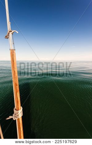 Boat hook on sailboat deck yacht, outdoor shot on blue sky background.