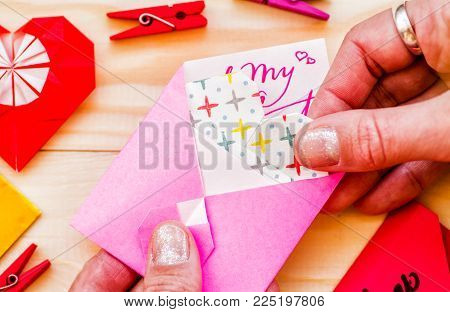 valentine's day concept. woman's hand putting an origami paper heart to a paper origami envelope