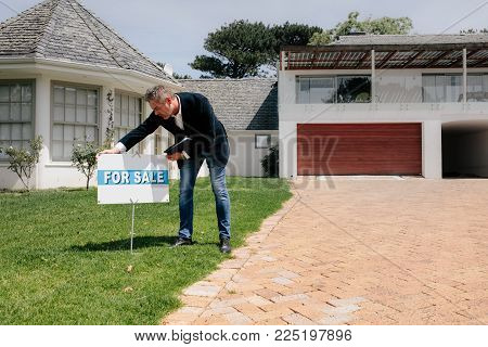 Real estate agent putting a for sale sign board outside a house. Male Real Estate broker with for sale notice in lawn of a new house.