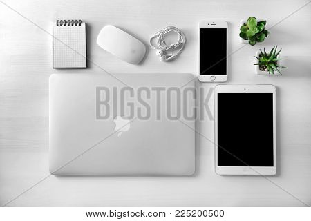 KYIV, UKRAINE - OCTOBER 23, 2017: Flat lay composition with Apple MacBook Air Silver, iPad mini 4 and iPhone 6s on wooden background