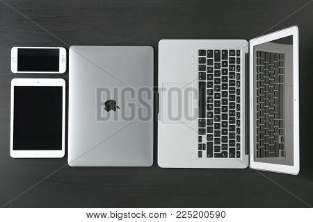 KYIV, UKRAINE - OCTOBER 23, 2017: Apple MacBook Air Silver, MacBook Pro Space Gray, iPad mini 4 and iPhone 6s on dark background