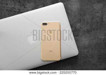 KYIV, UKRAINE - NOVEMBER 21, 2017: MacBook and iPhone 7 Plus Gold on grey background