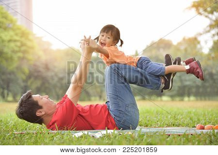 Happy young Asian father and his daughter lying on the grass and playing together in nature at park outdoor. Family Having fun.