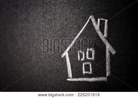 House drawing on blackboard. Home shape on chalkboard