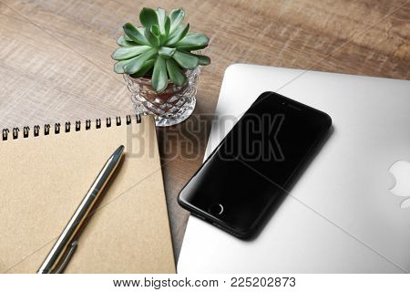 KYIV, UKRAINE - DECEMBER 18, 2017: Modern iPhone 8 Space Gray notebook and laptop on table