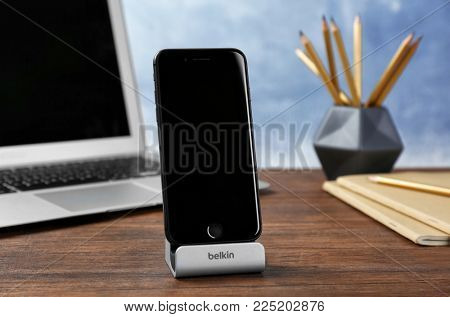 KYIV, UKRAINE - DECEMBER 18, 2017: Modern iPhone 8 Space Gray with Belkin stand on table