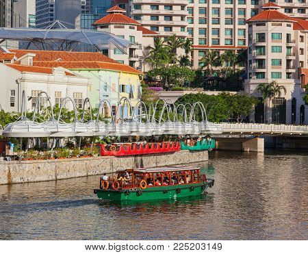 CLARKE QUAY, SINGAPORE - AUGUST 17, 2009: A traditional bumboat on the Singapore River passes Clarke Quay, with a hotel in the background.