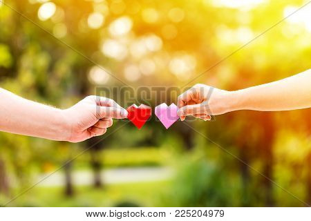 A man and woman hand holding a red heart and pink heart with love.