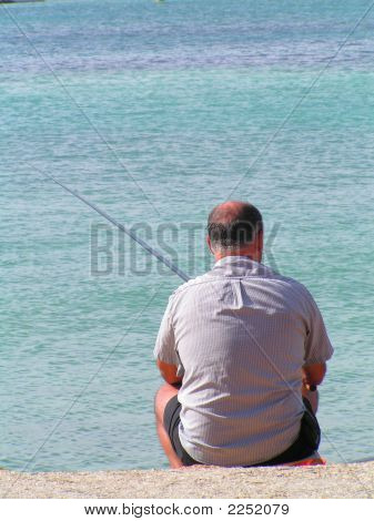 A Fisherman fishing near the Delimara Powerstation. poster