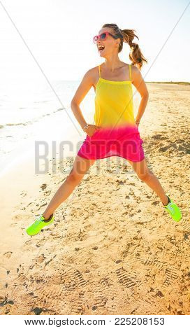 Happy Trendy Woman On Seacoast In Evening Jumping
