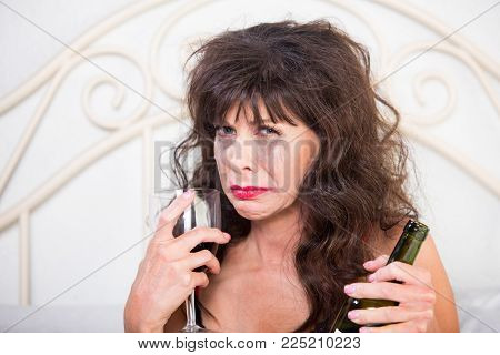 Closeup of upset mature woman crying and drinking wine in her bedroom
