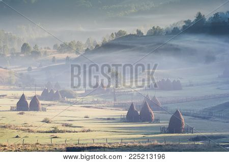 Beautiful rural mountain landscape in the sunrise light with morning fog, Fundatura Ponorului, Hunedoara County, Romania